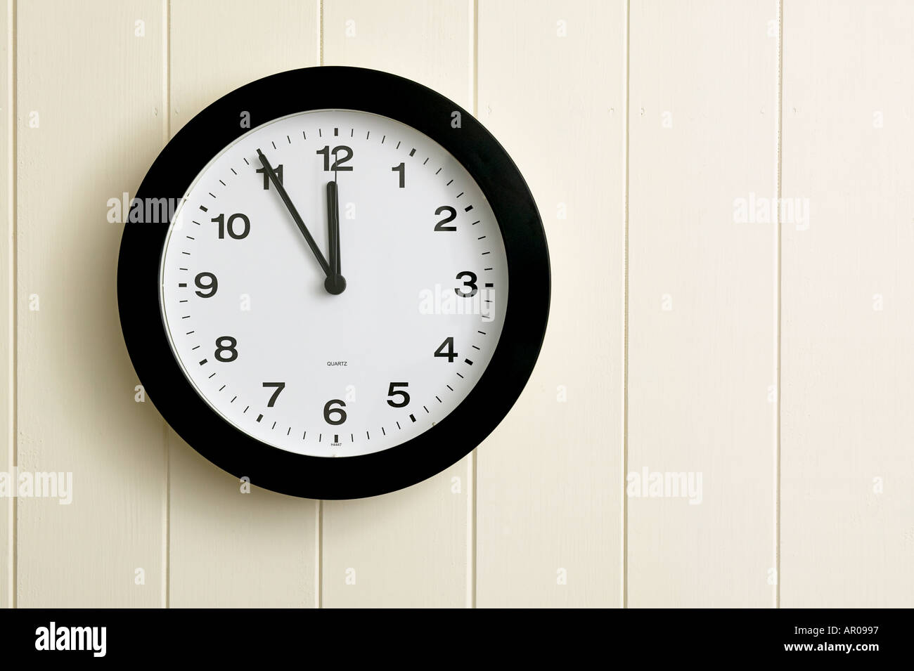 wall clock showing time at five to twelve 1155 2355