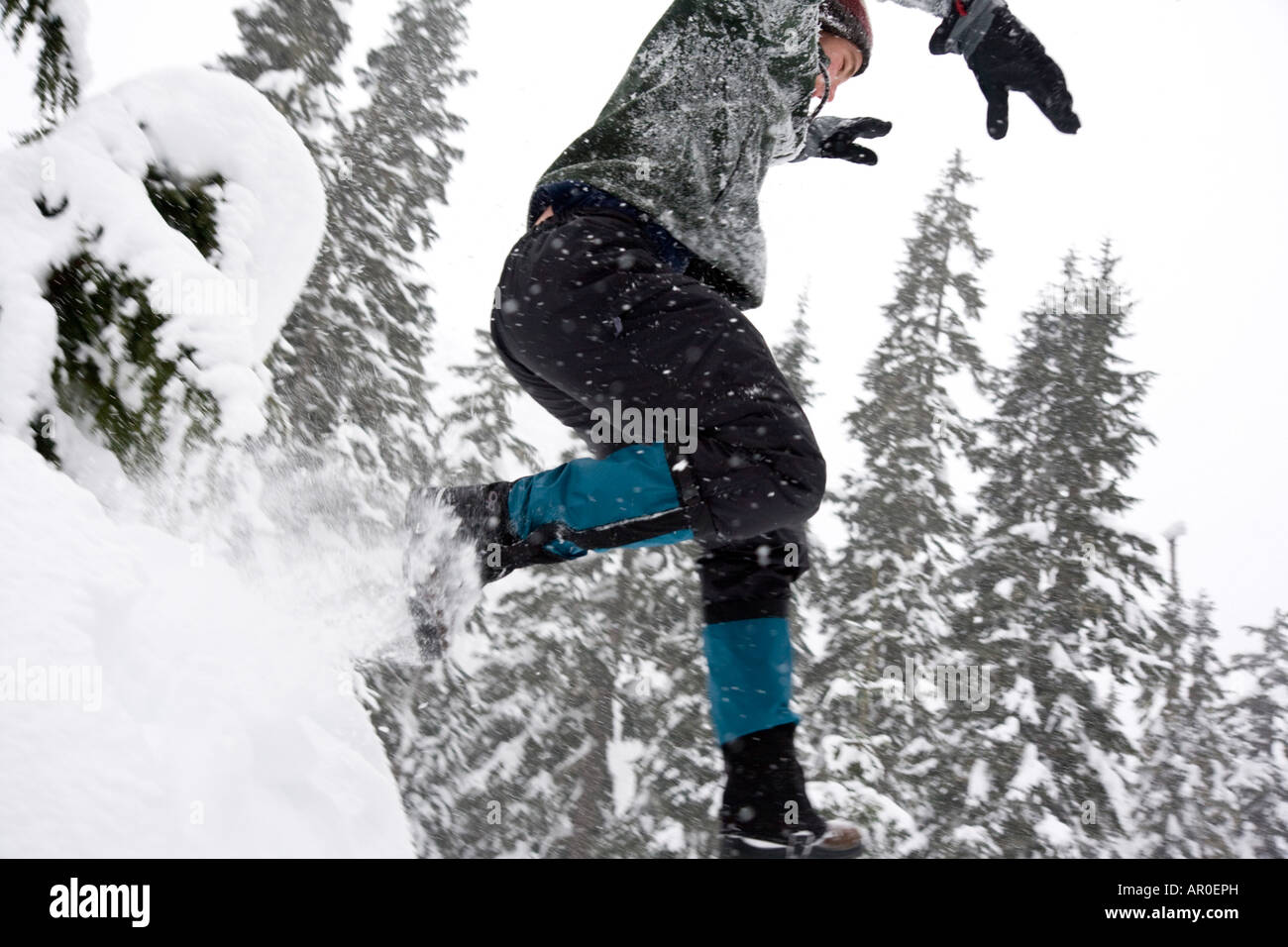 A male snowshoer jumps off a snow mound. - Stock Image