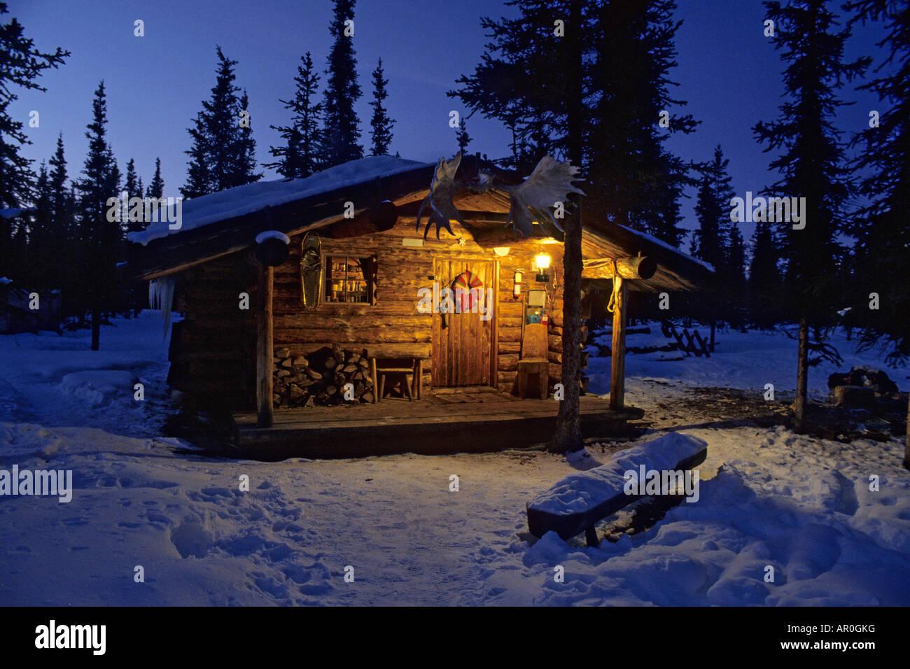 interior alaska log cabin forest winter porch light snow sky dusk