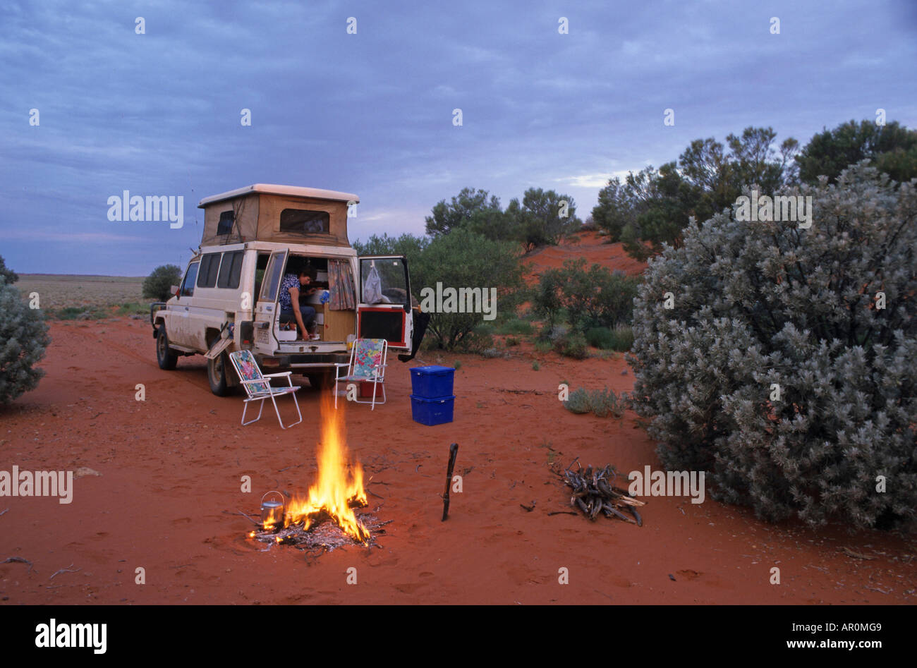 Four-wheel drive on red track, red centre, Australia, Four-wheel drive and campfire, camping in red sand dunes, Stock Photo