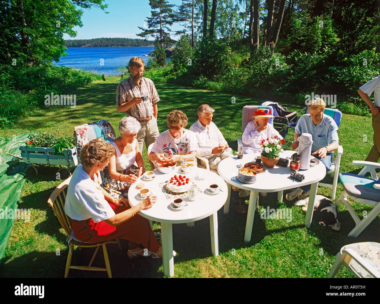 Friends sharing food, coffee and conversation on family owned island in Stockholm Archipealgo Stock Photo