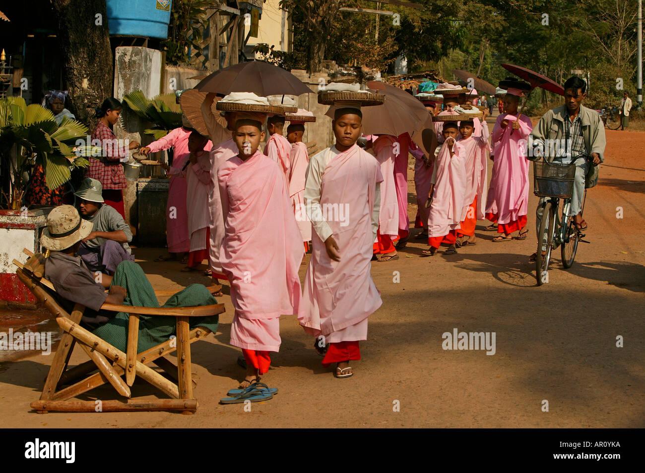 Nuns walk in a line to collect alms, Bago, Nonnen in rosa Roben, gehen in Reihe, Almosen sammeln, bekommen ungekochten Reis, Moe - Stock Image