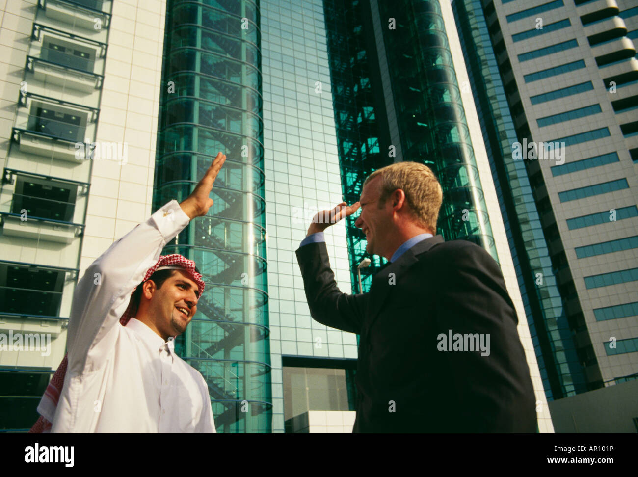 Arab men greeting other stock photos arab men greeting other stock an arab and a businessman greeting each other happily near a commercial complex stock m4hsunfo