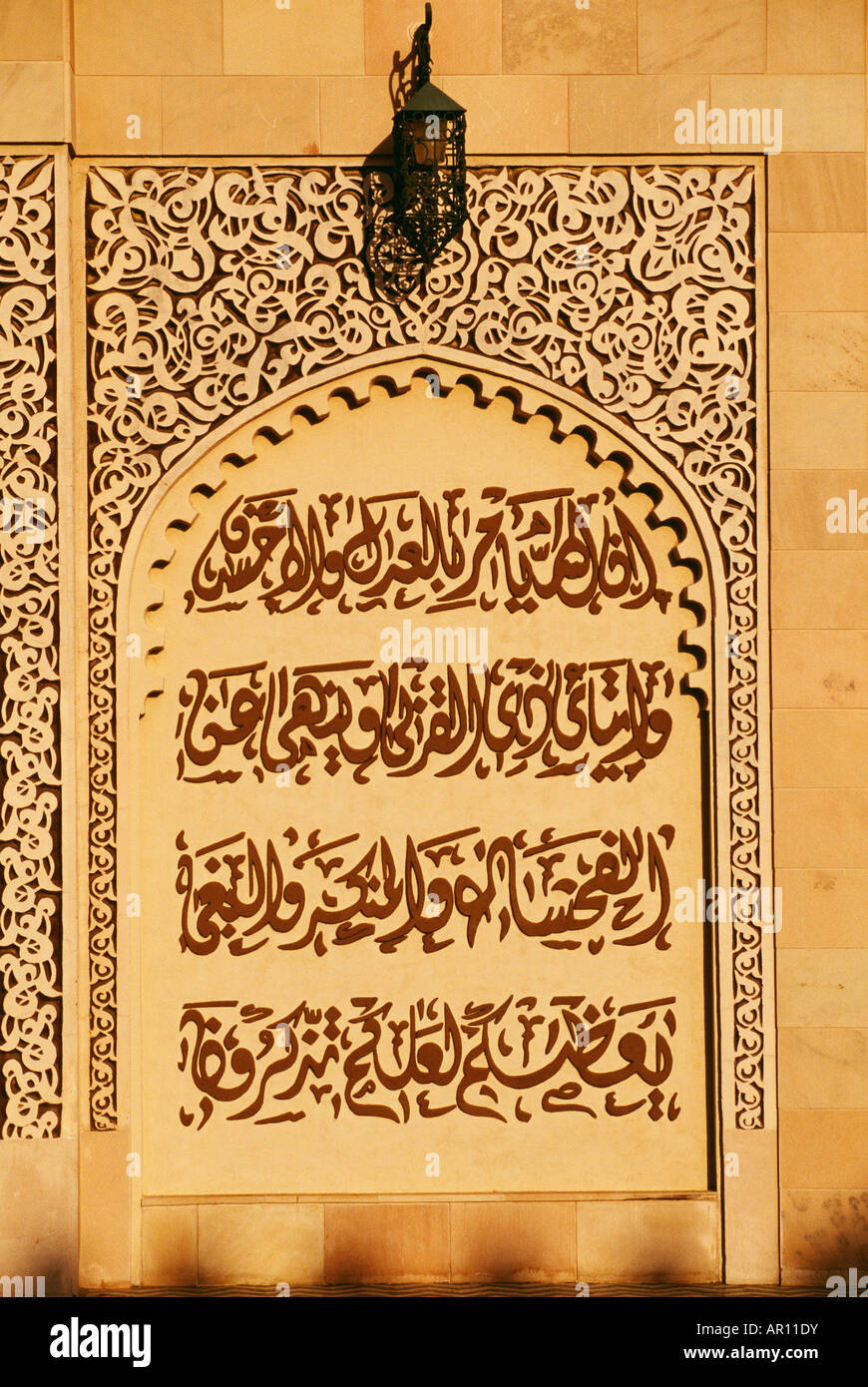 A lamp is seen above a scripture in Urdu on a wall. - Stock Image