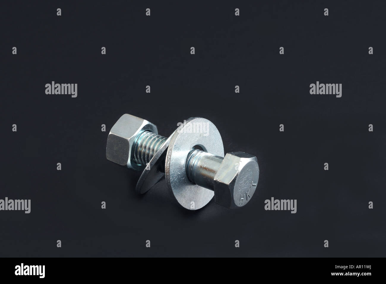 A bolt with washers and nut attached. - Stock Image