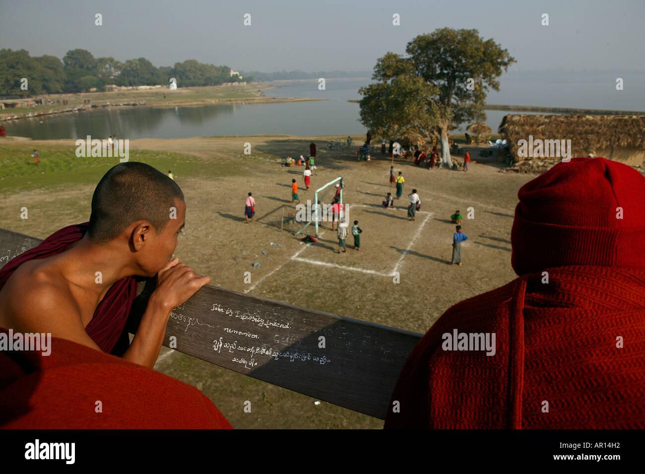 Monks watch football match from U Bein bridge, Moenche beobachten Fussballspiel von der U Bein Bruecke, Amarapura bei Mandalay - Stock Image