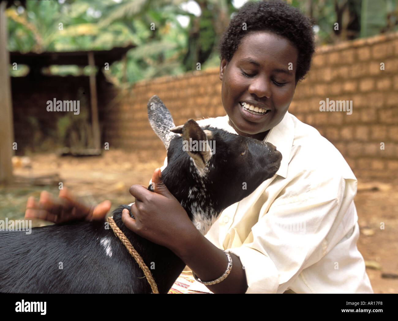 Rwanda genocide orphan Angelique looks after her 4 youger siblings relieved to receive a goat from Send a Cow to provide mil - Stock Image