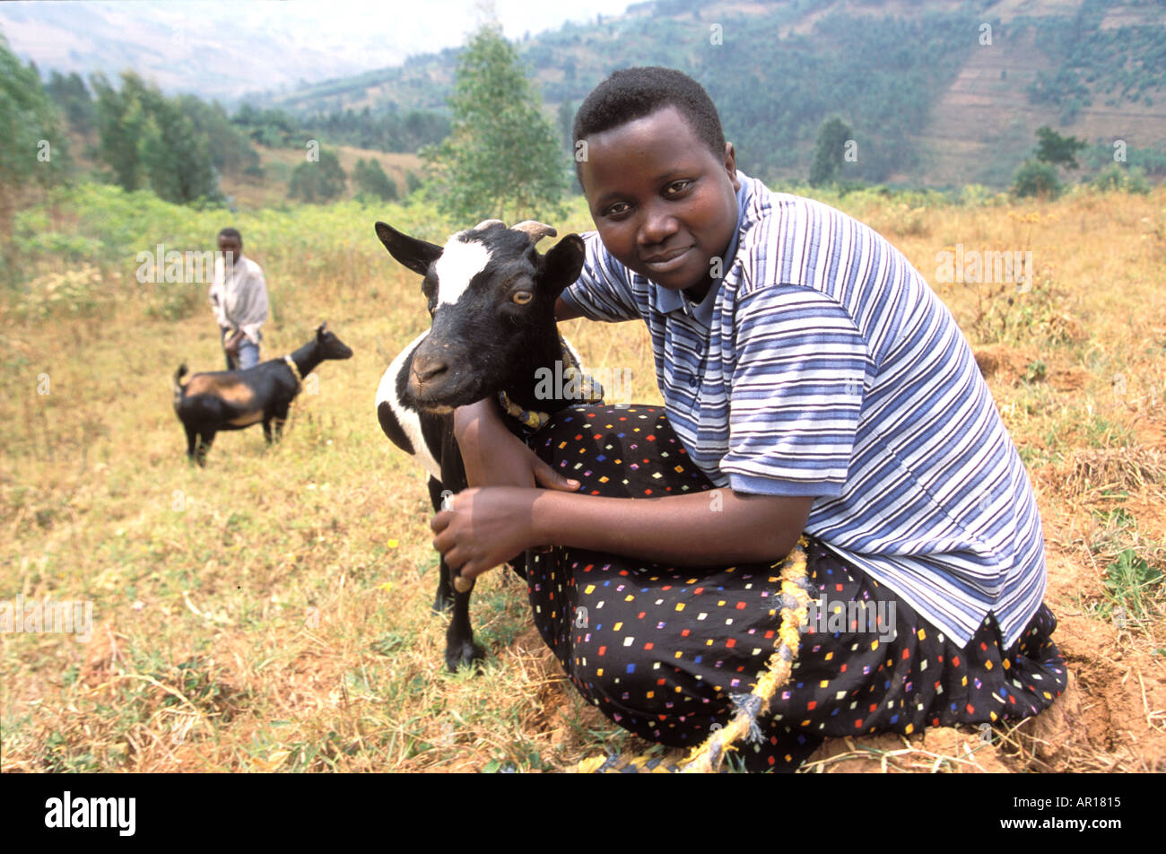 Rwanda genocide orphan Sylvie who is mother to her younger siblings is given a goat by Send a Cow for milk mountains poor sad - Stock Image
