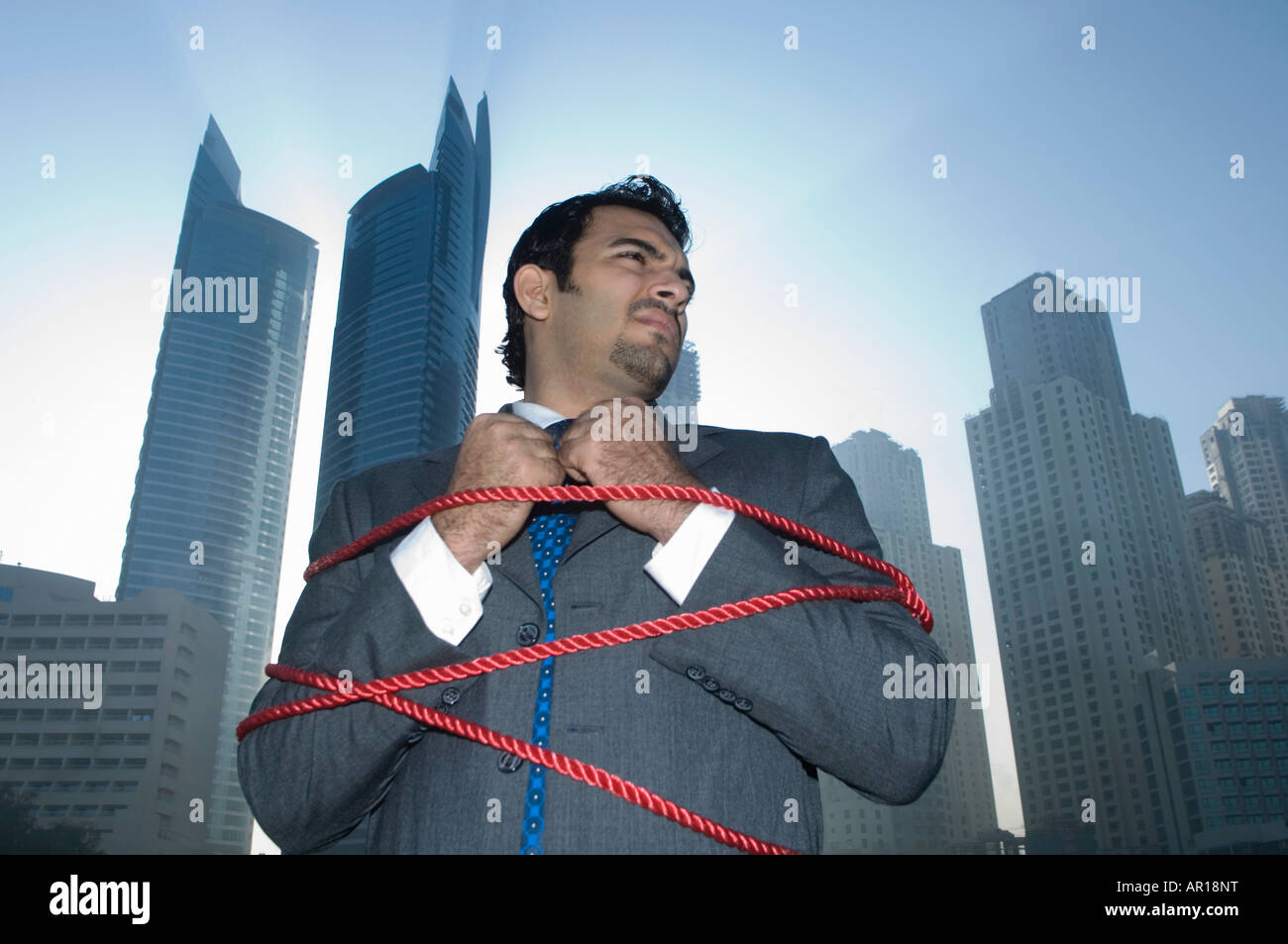 Businessman tied with rope, towers seen through the mist in the background Stock Photo