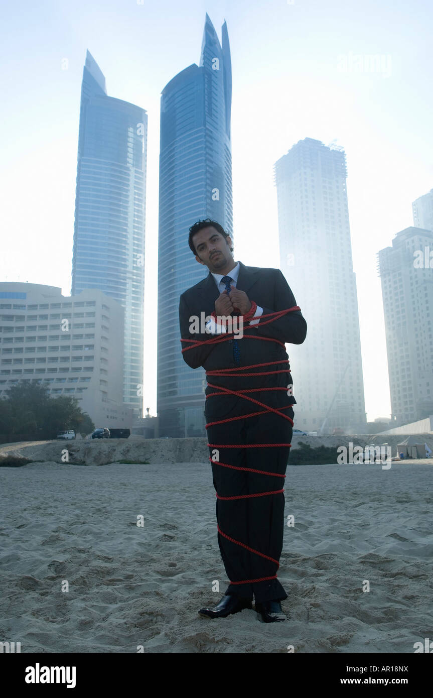 Businessman tied with rope, towers seen through the mist in the background - Stock Image