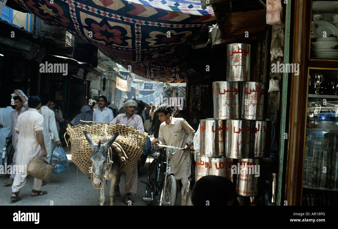 A donkey and cart negotiate the lanes of Peshawar To deliver some cans of Unilever Lotus Oil.This is near Ander - Stock Image