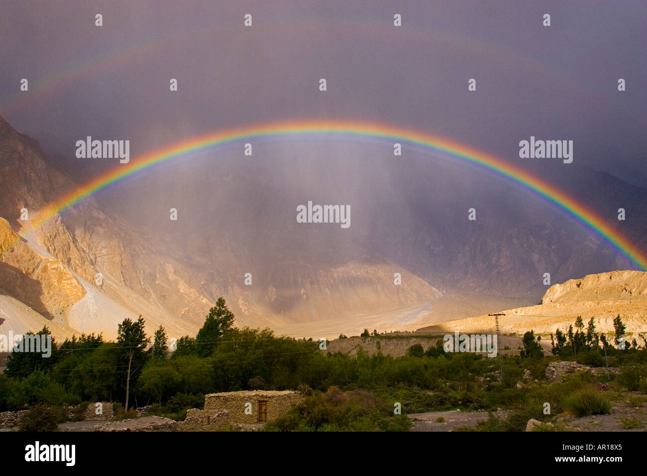 A stunning rainbow after a rainstorm over the village and the peaks of Passu Pakistan - Stock Image