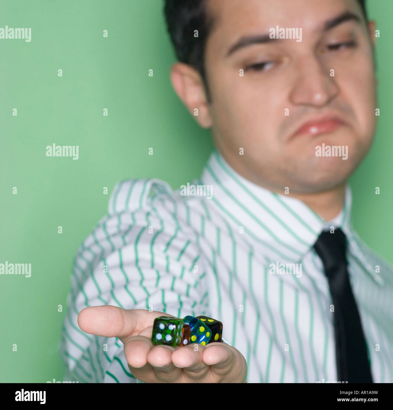 Young man showing group of dice with a sad expression - Stock Image