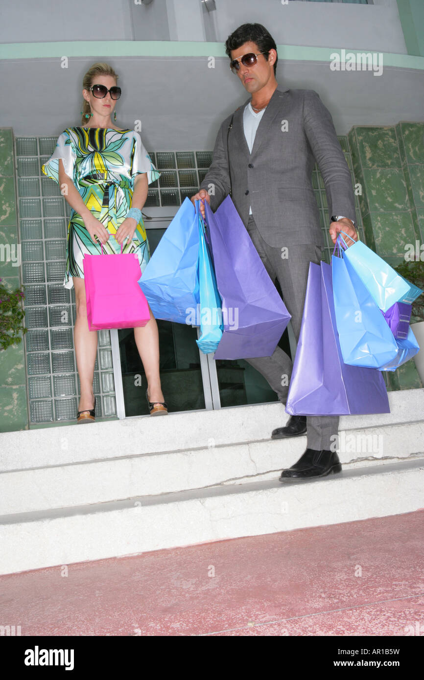 Fashionable couple with shopping bags outside of hotel. - Stock Image