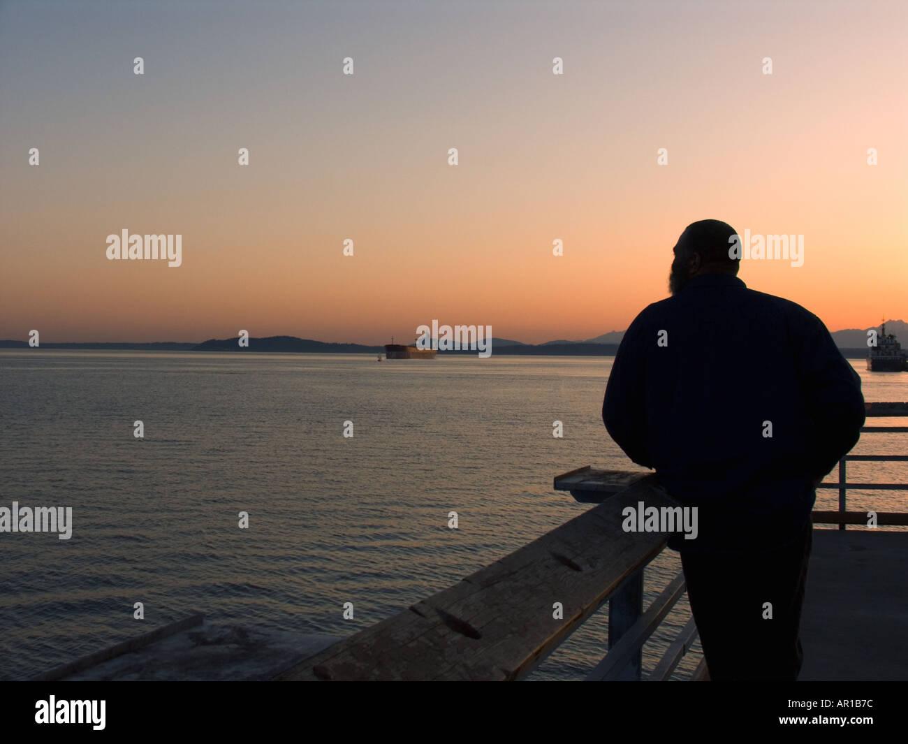 Man on public fishing pier watching sunset on Seattle Waterfront at Myrtle Edwards Park Seattle Washington - Stock Image