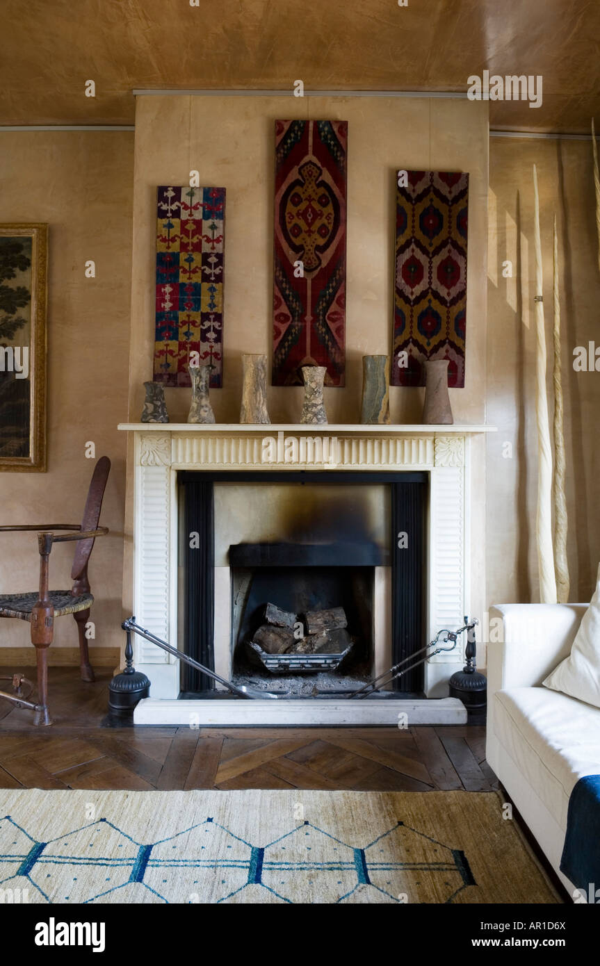 fireplace with tribal artefact's and wall hangings in antique collector's house in London - Stock Image