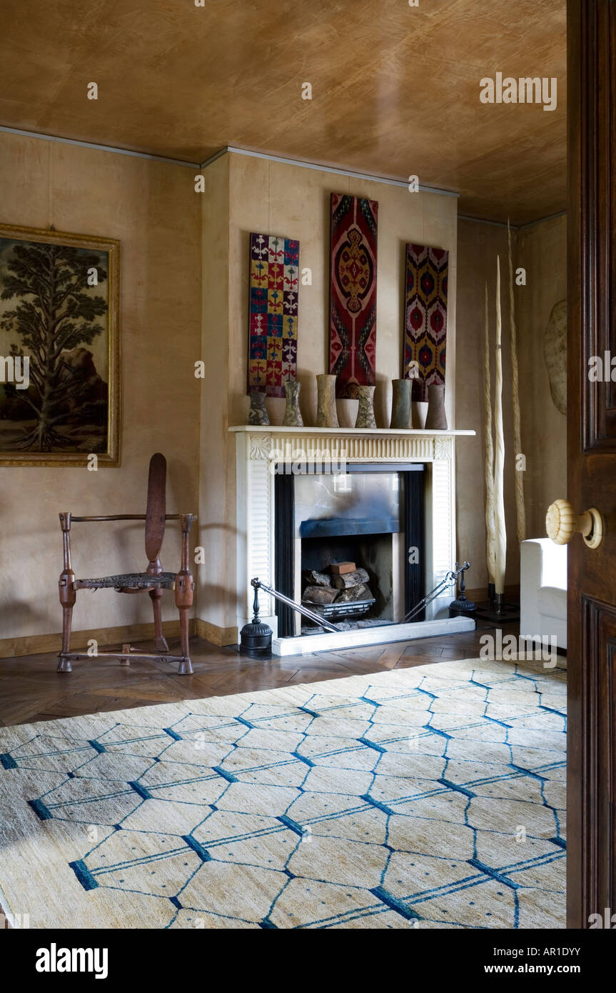 Fireplace with tribal ceramic display and wall hangings - Stock Image