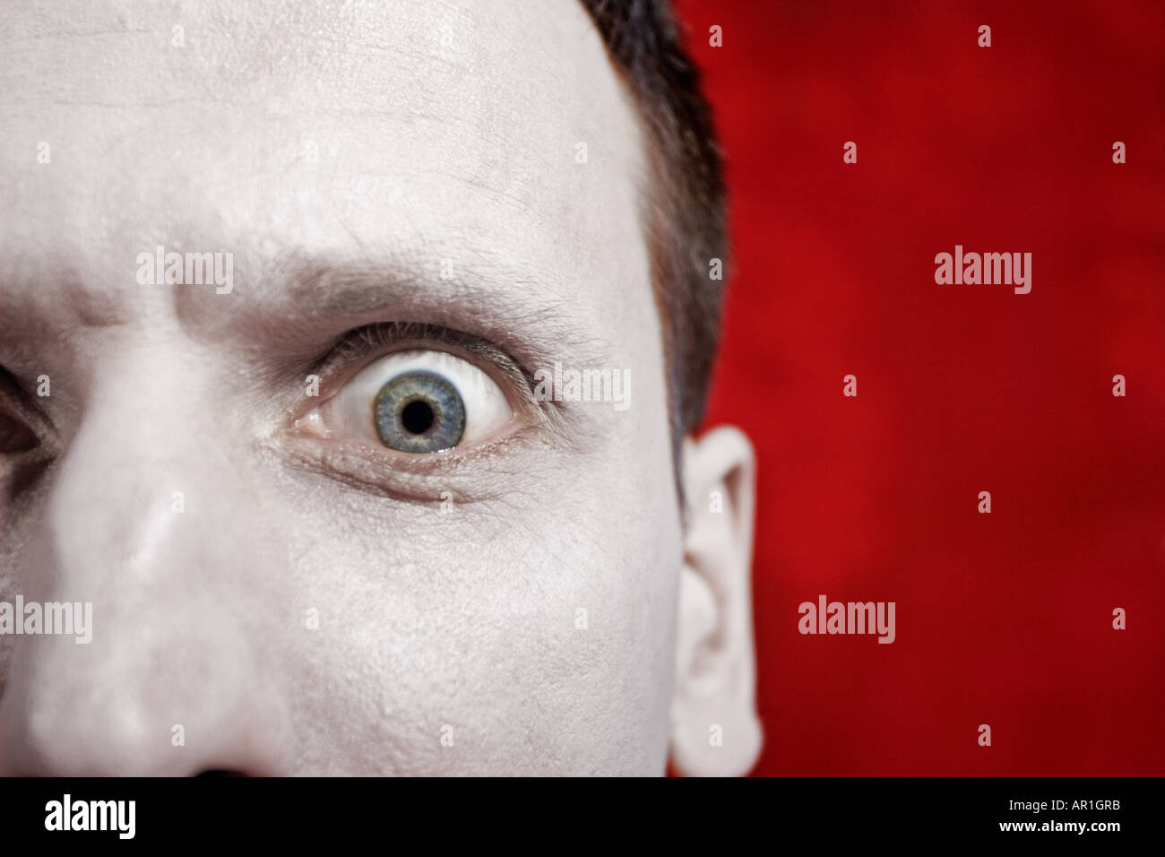 indoor flat room man mature 35 40 dark haired fragment face nose eye open wide facial expression mime scarry scared fear clos - Stock Image