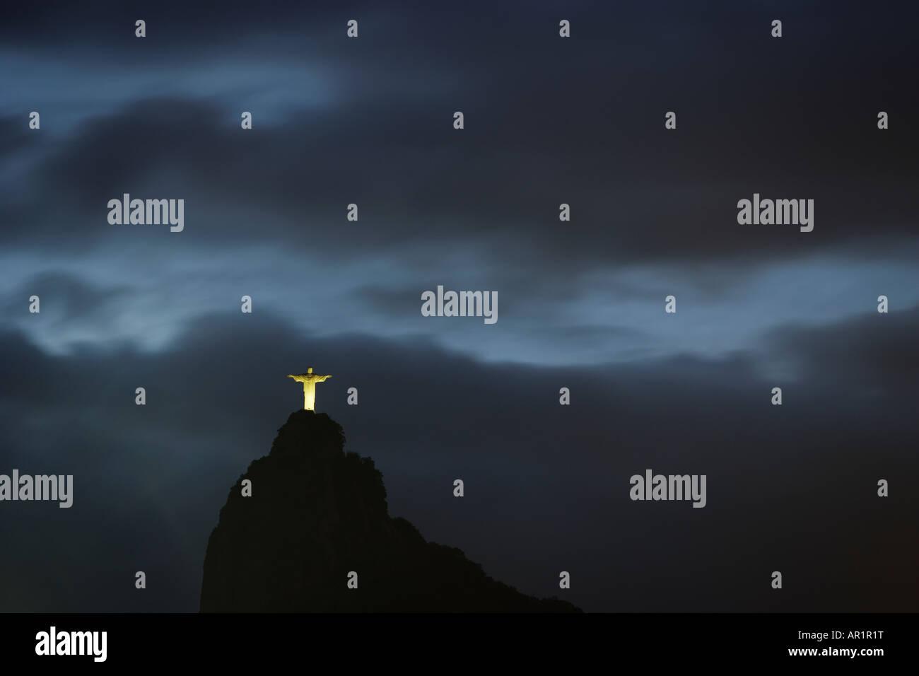 Sun setting and grey sky behind Corcovado Cristo Redentor Christ the Redeemer in Rio De Janeiro Brazil - Stock Image