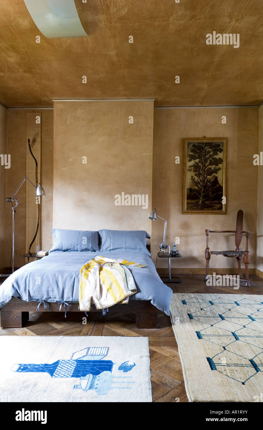 bedroom with stucco finish walls and Afghan carpet - Stock Image