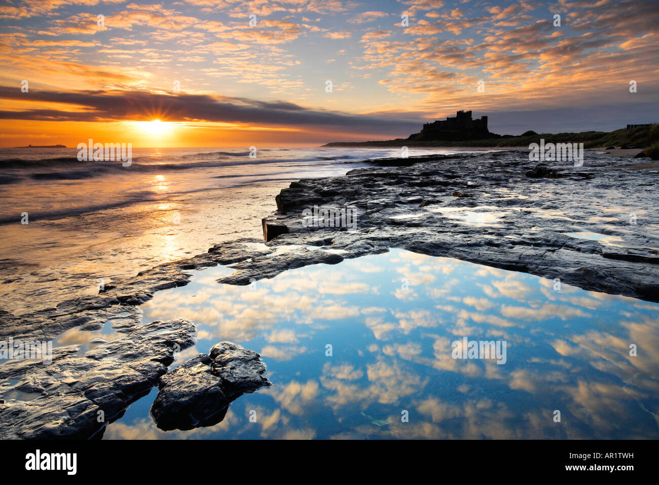 Spectacular sunrise on the coast near Bamburgh Castle, Northumberland - Stock Image