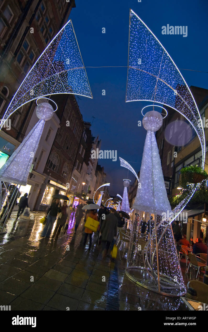 vertical wide angle of abstract christmas angel lights and lots of shoppers in central london in the rain at night