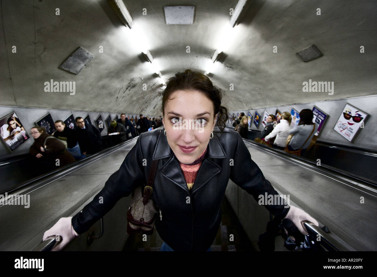 Woman on escalator leading to an London Underground tube station Only woman in foreground is model released 12 06 - Stock Image