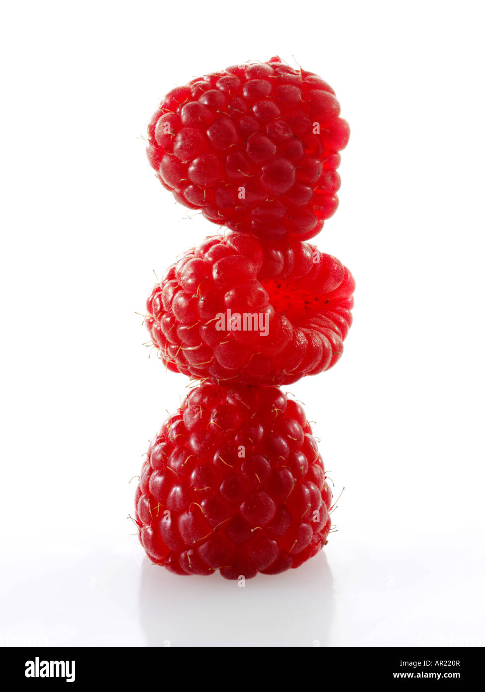 close up of a stylised stack of raspberries standing onto of each other - concept creative photo against a white - Stock Image