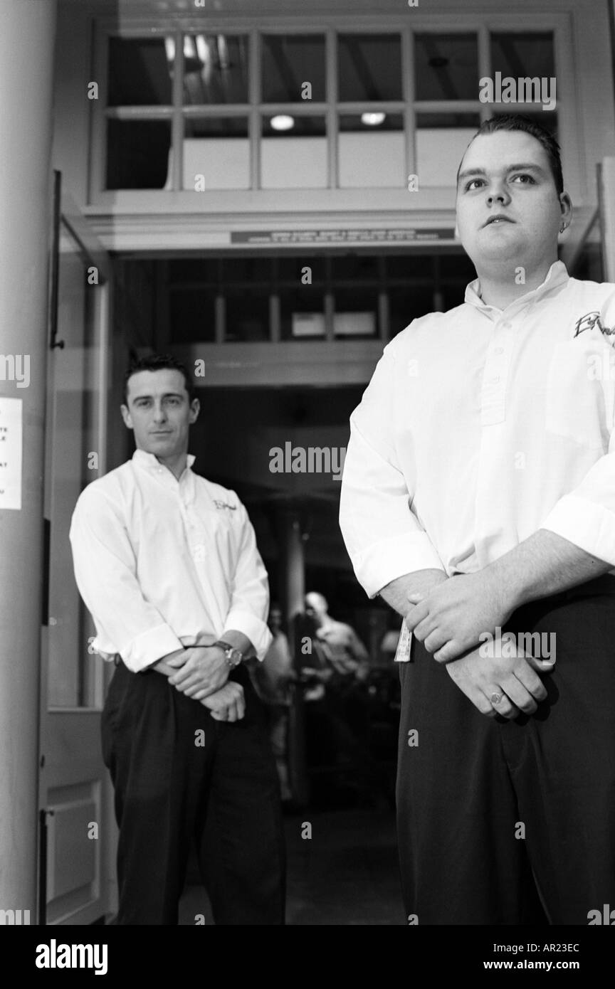 two male doormen bouncers outside pub black and white monochrome