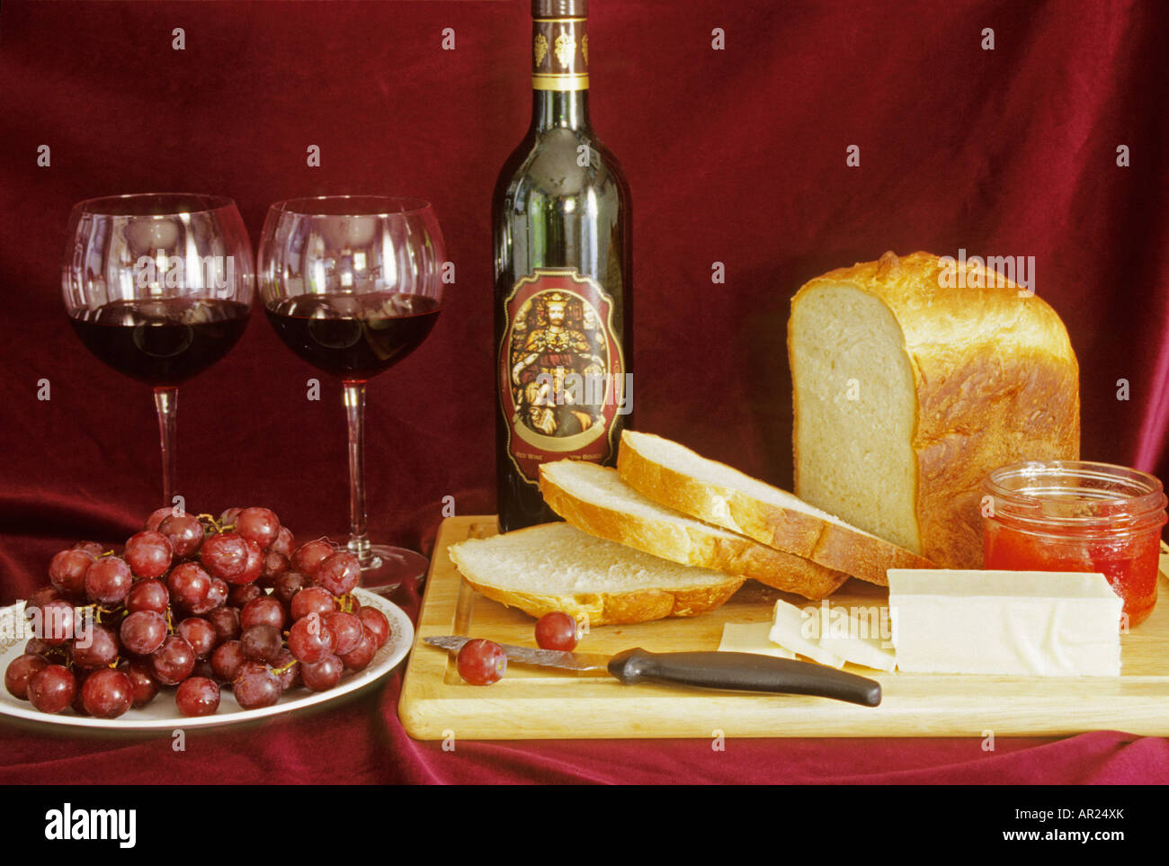 Still life table setting of bread, wine, cheese, jam, grapes - Stock Image