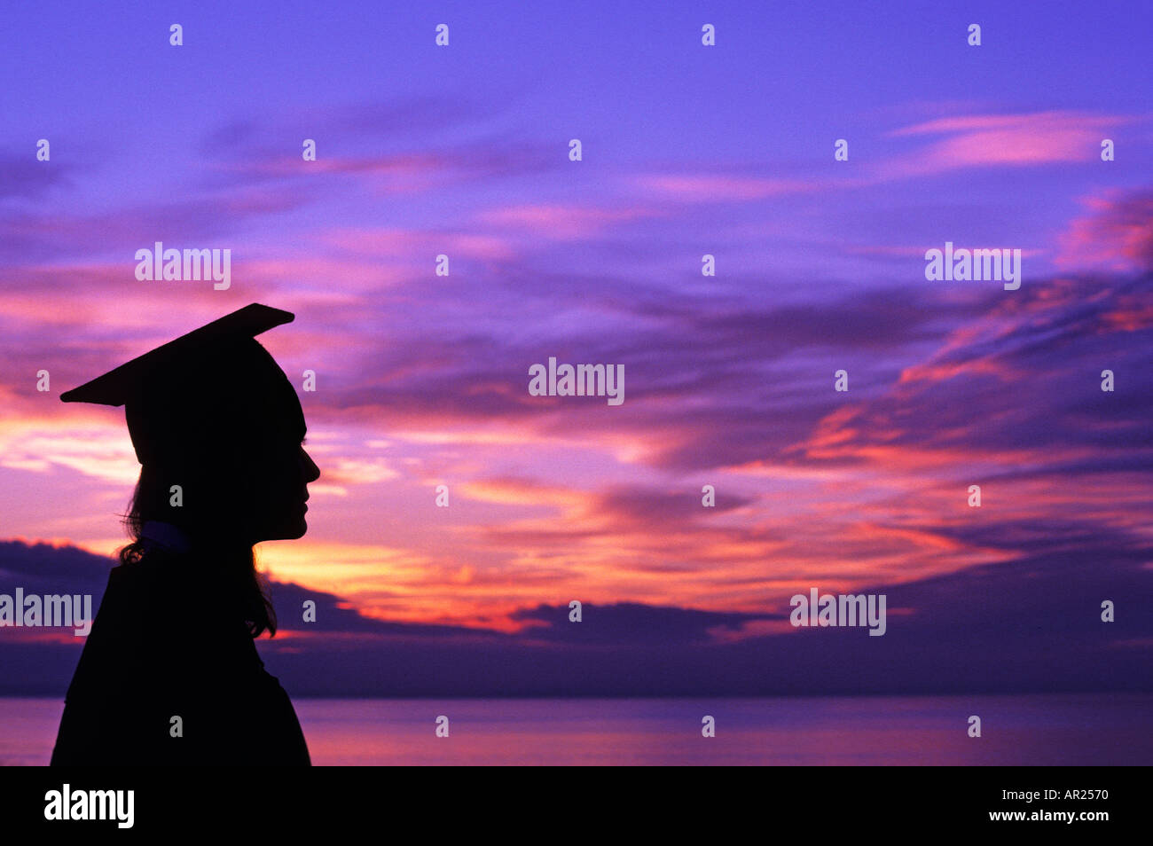 Female graduate in cap and gown silhouetted against colorful sky and sea in background 1902 015 11 Stuart Dee - Stock Image