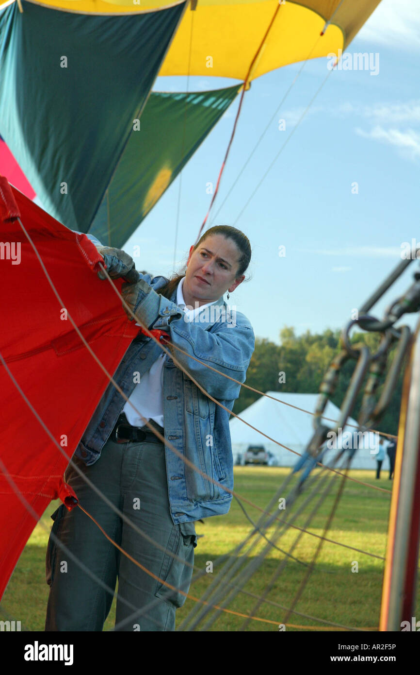 female ground crew holding the balloon open so the hot air can inflate the balloon Balloon Reg No. G-CCKY Stock Photo