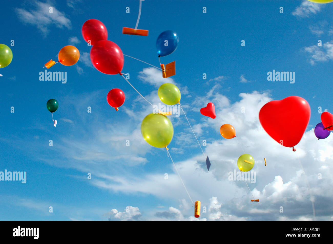 Colored helium balloons with messages floating in the sky above Stock Photo