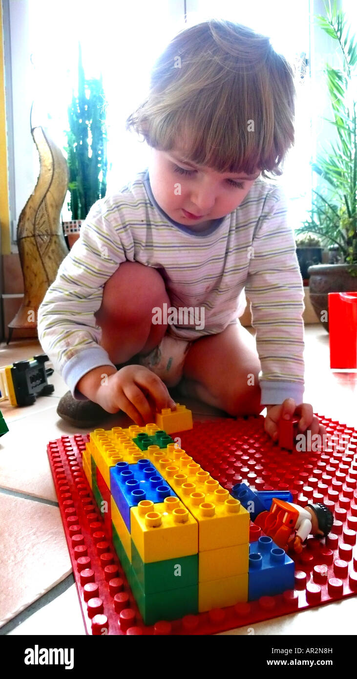 little boy playing with Lego bricks Stock Photo