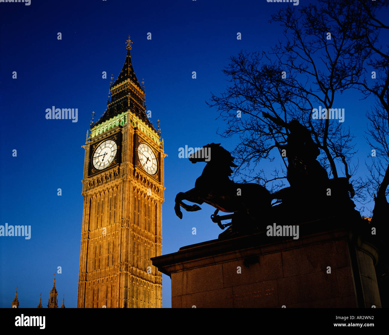 Big Ben clock floodlit at night, with the Statue of Boadicea silhouetted on the embankment at  Westminster, England, United Kingdom, UK, GB - Stock Image