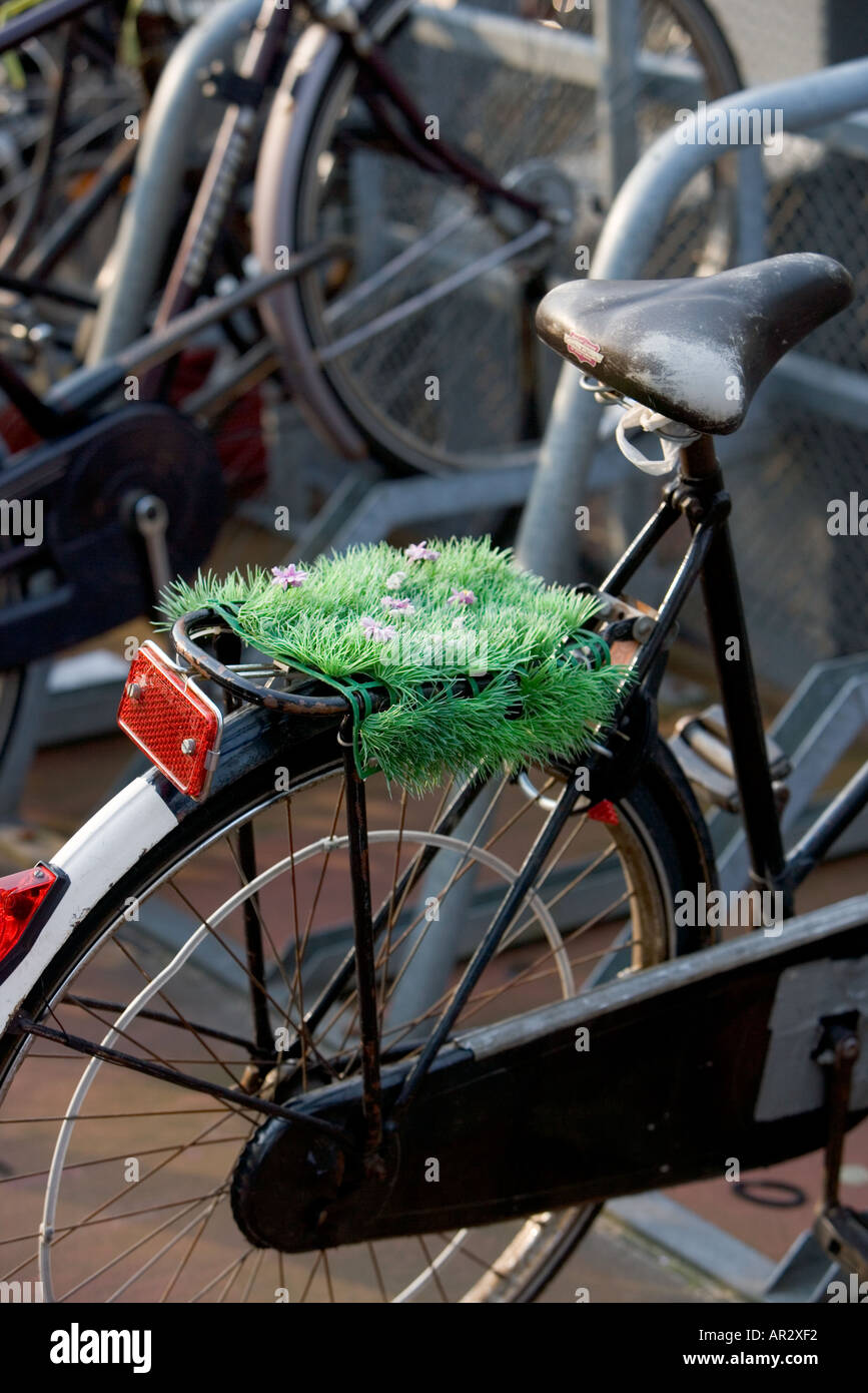 HOLLAND AMSTERDAM BIKE PARKED IN MULTI STOREY BIKE PARK WITH PLASTIC GRASS AND FLOWERS ON THE BACK CARRIER - Stock Image