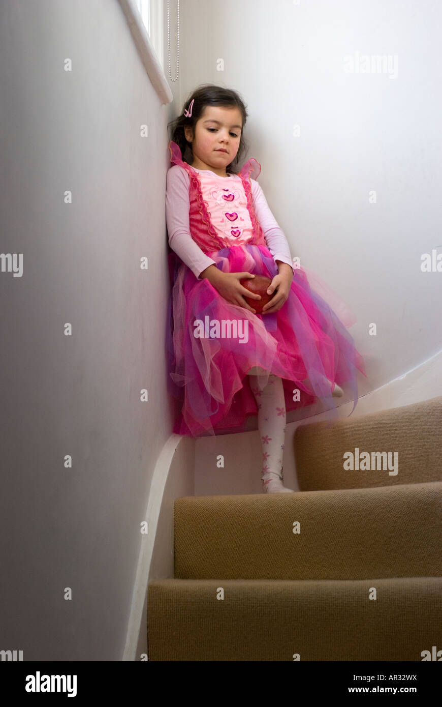 Moody child on staircase - Stock Image