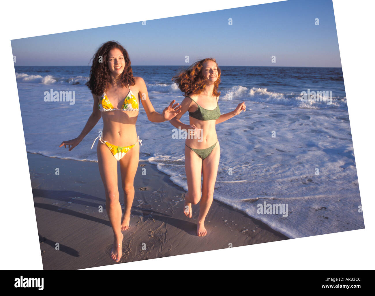 Girls 2 girls running on beach h - Stock Image