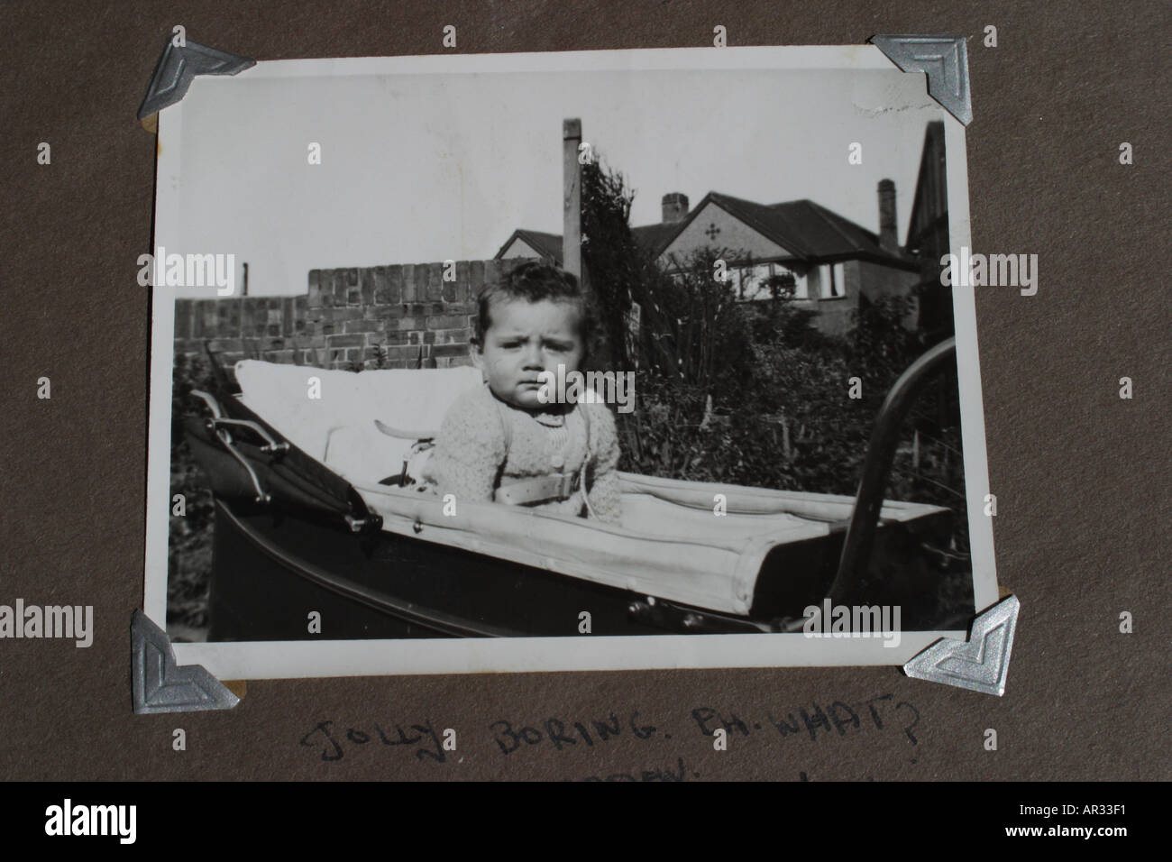 Nostalgia old black and white photograph showing baby aged 6 months old in old fashioned large pram taken in mid 1950s