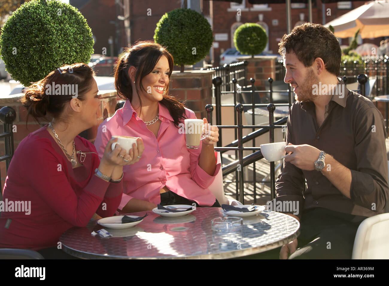 Three Friends Two Young Ladies And One Man Drinking Coffee And Stock Photo Alamy