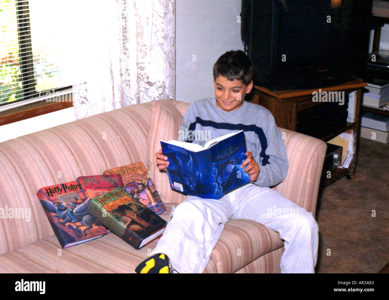 Enthusiastic young reader is enthralled with his copy of the fifth Harry Potter book - Stock Image