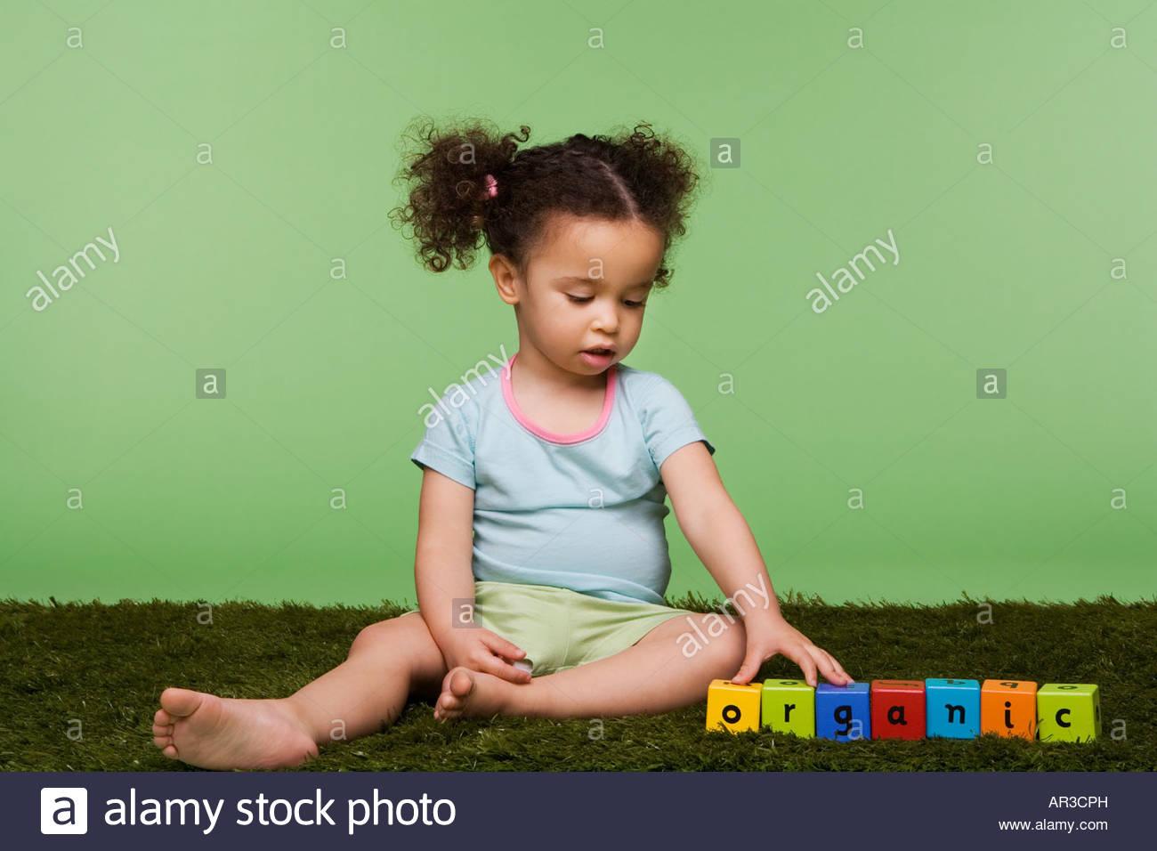 Girl with building blocks spelling organic - Stock Image