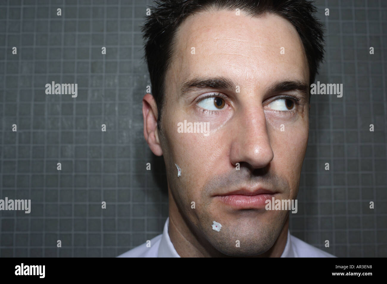 Portrait of a young businessman with shaving cuts and tissue on his face in bathroom - Stock Image
