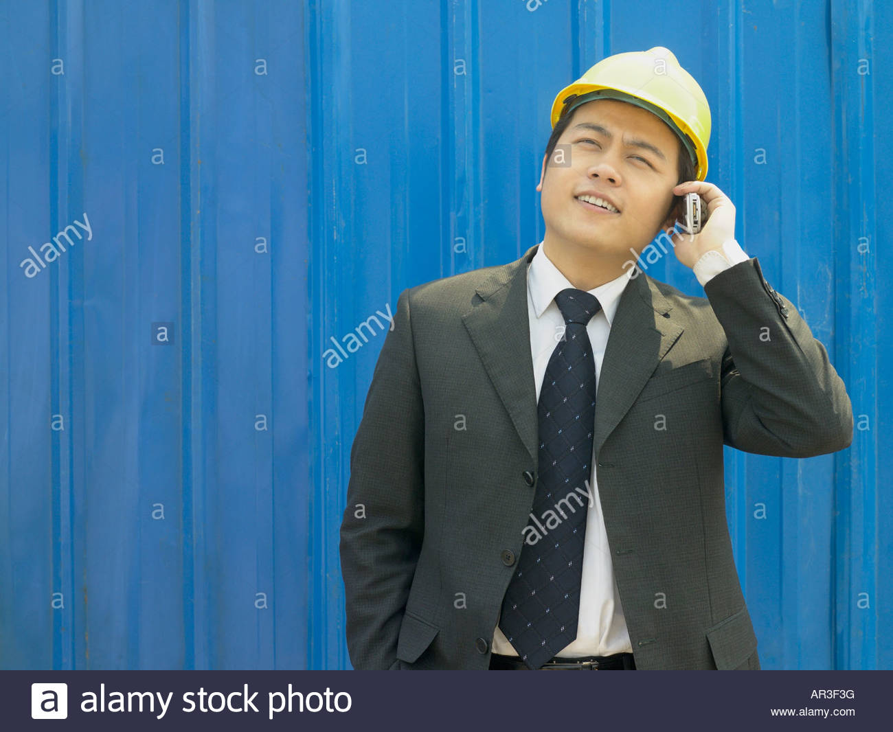 Businessman in hard hat with cellphone - Stock Image