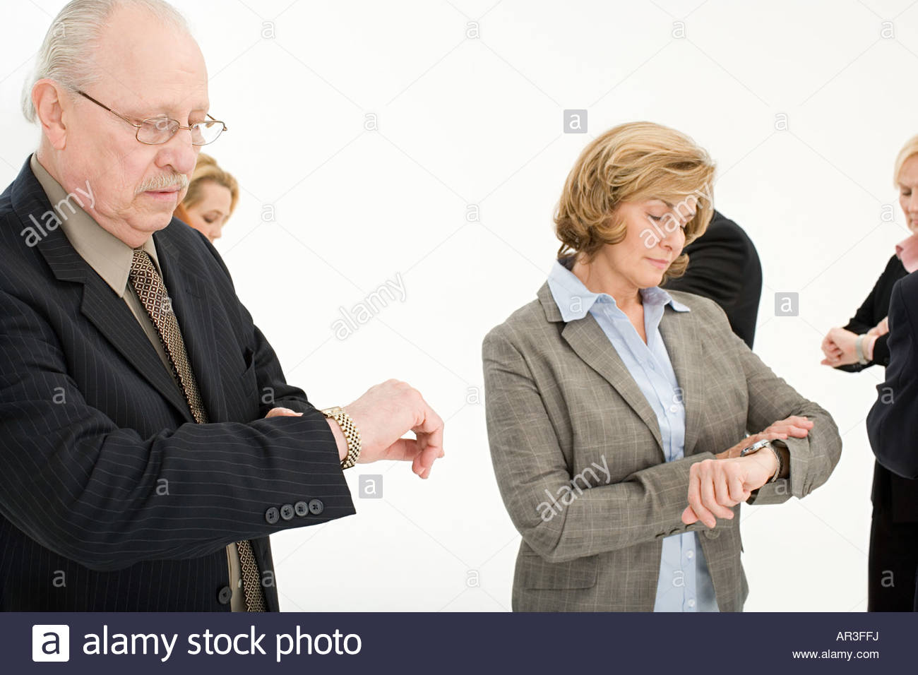 Businesspeople looking at their watches - Stock Image