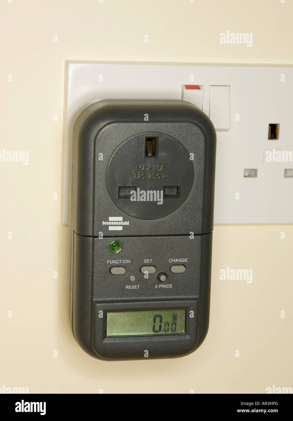 digital energy meter in wall socket to measure electricity consumed by a plugged in appliance - Stock Image