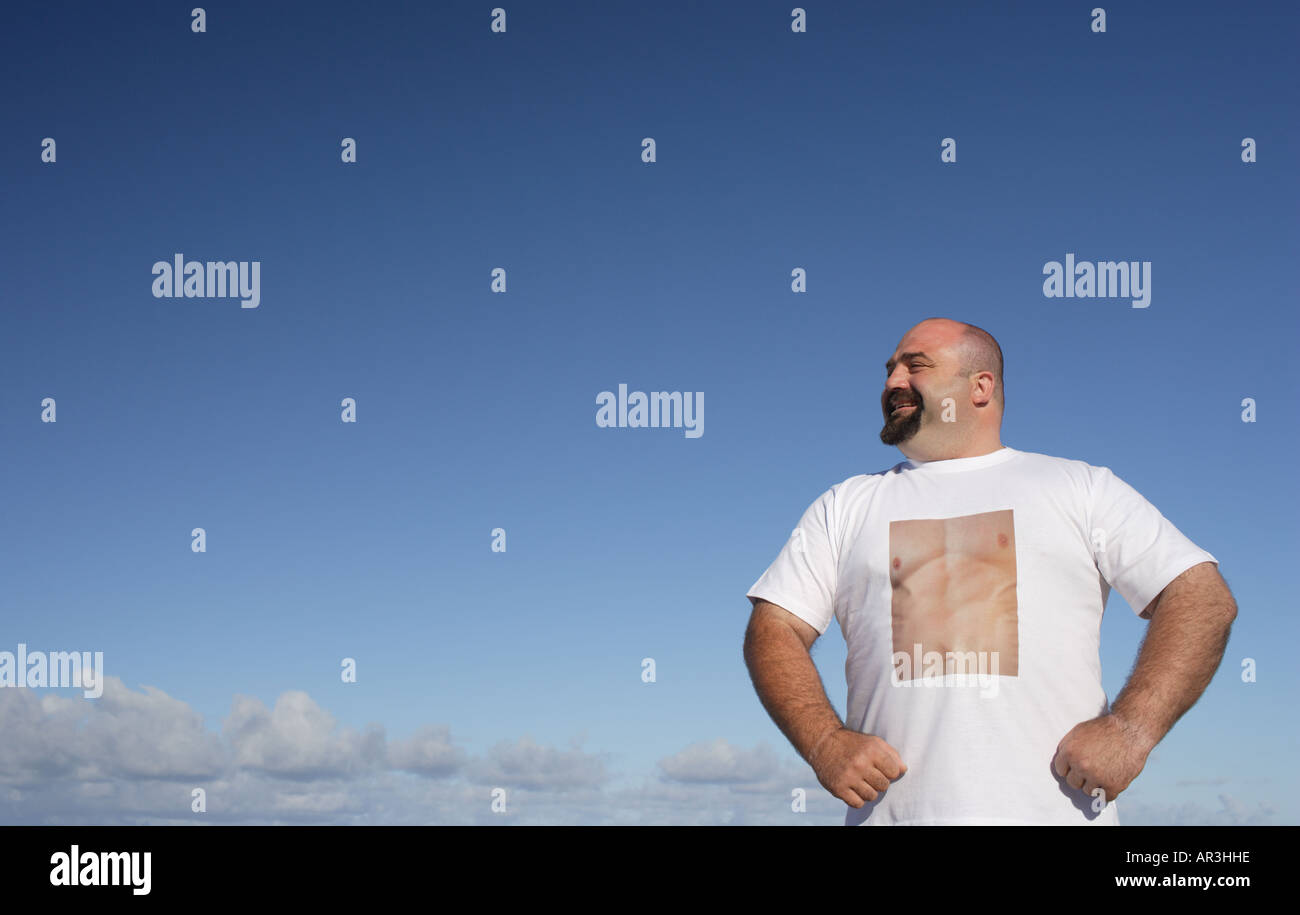 Man wearing t-shirt displaying a perfectly toned chest standing against blue sky - Stock Image