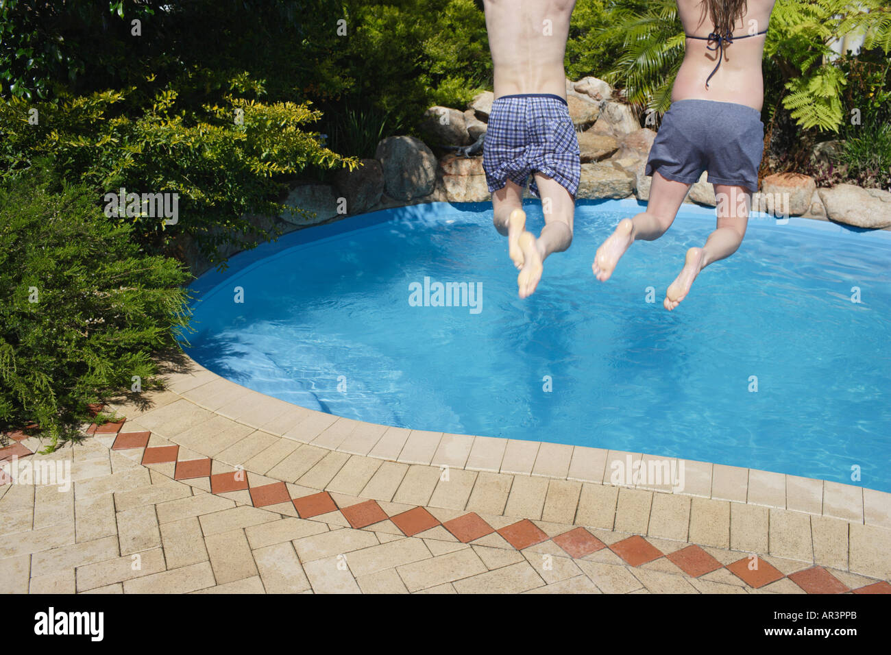 Young couple jumping into outdoor swimming pool - Stock Image