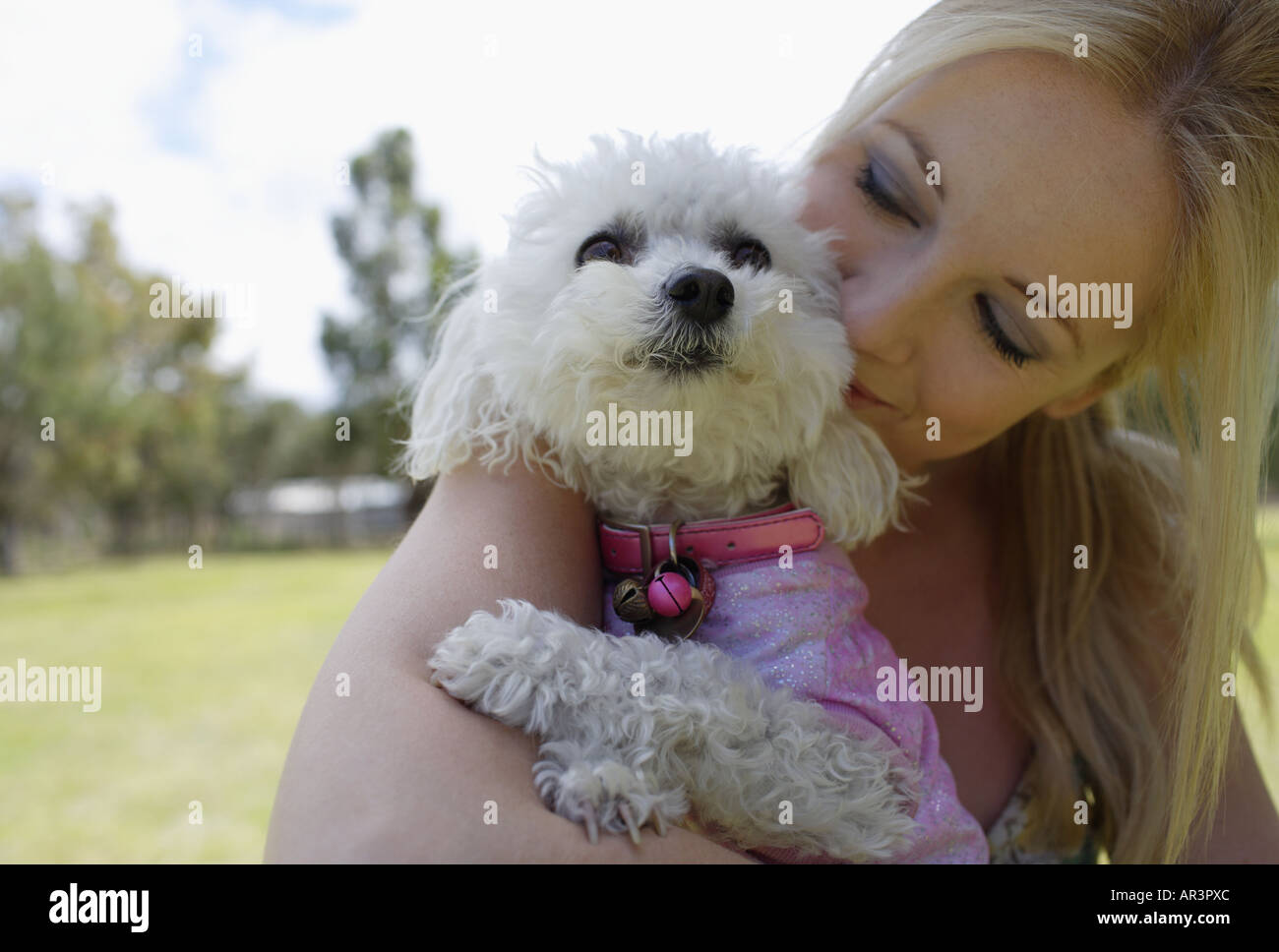 Young woman cuddling pet dog in park - Stock Image