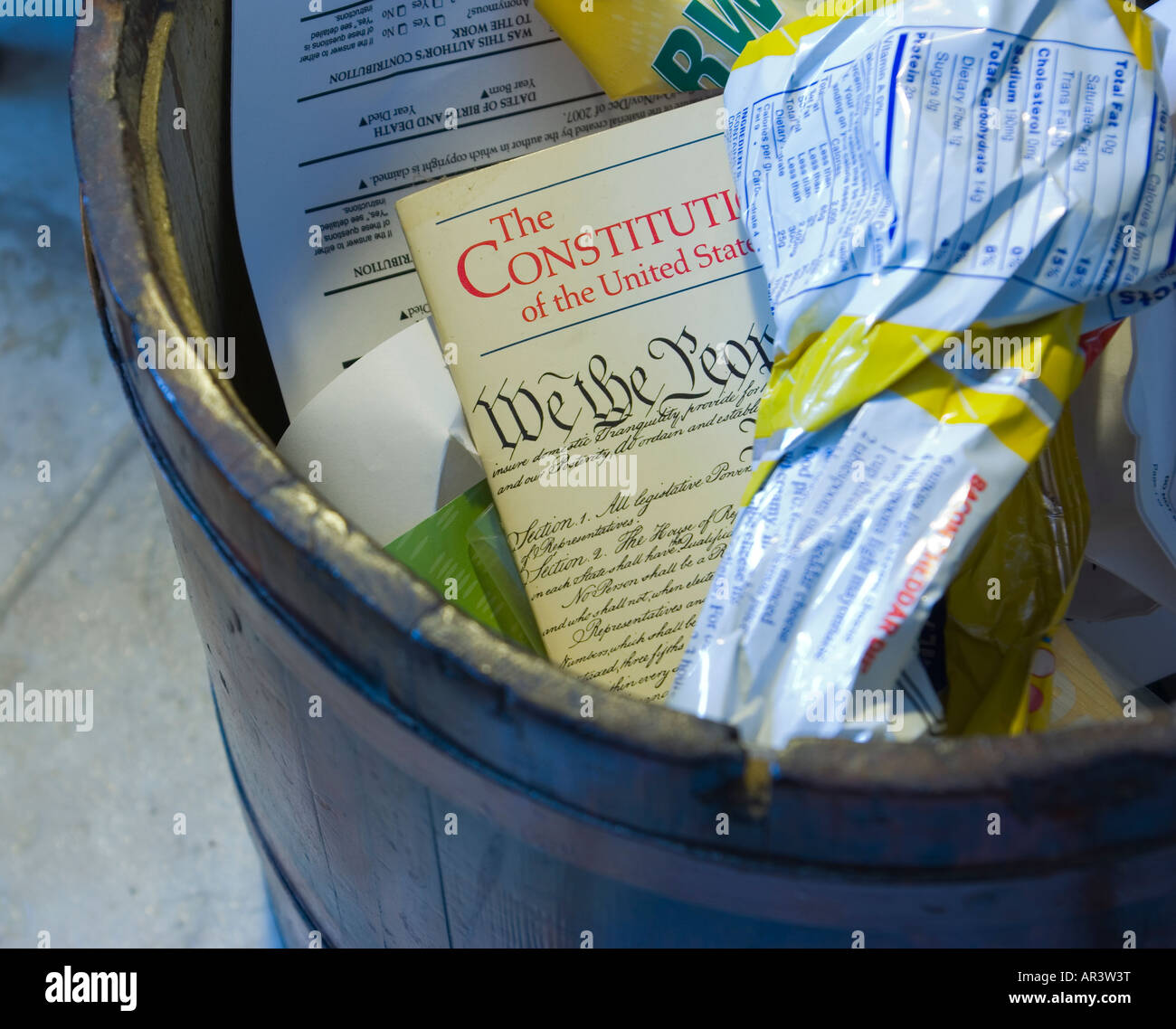 Small copy of U S Constitution shown in wastepaper basket with other refuse - Stock Image